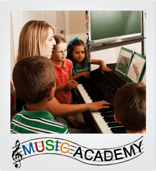 Music Academy Classes: a teacher shows children a begginer song. Free preview classes in August!